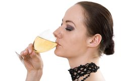 Woman Drinking Wine. Young adult woman holds a glass of white wine to her lips taking a sip.  Head shot shows woman in profile with hair pulled back and a beaded Royalty Free Stock Images