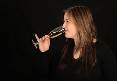 Woman drinking wine. Side view of pretty young woman drinking glass of wine, black background Stock Image