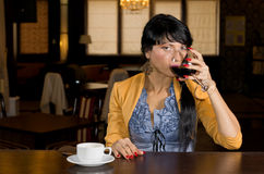 Woman drinking wine and coffee at a bar counter. Attractive young woman drinking wine and coffee at a bar counter sipping from a large wineglass while glancing royalty free stock photos