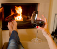Woman drinking wine in front of fire Royalty Free Stock Photos