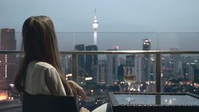 Woman Drinking Wine. Happy woman drinking a glass of white wine while sitting in rooft bar in the city or on the terrace with cityscape at sunset. Vacation stock video