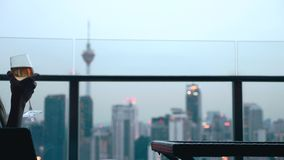 Woman Drinking Wine. Happy woman drinking a glass of white wine while sitting in rooft bar in the city or on the terrace with cityscape at sunset. Vacation stock footage