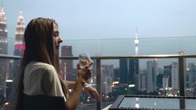 Woman Drinking Wine. Happy woman drinking a glass of white wine while sitting in rooft bar in the city or on the terrace with cityscape at sunset. Vacation stock video footage