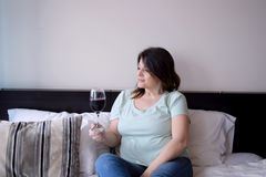 Woman drinking wine on her bed Royalty Free Stock Photo