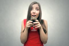 Woman drinking wine from wineglass. Wine degustation. Surprised enraptured woman is holding in hands a wine glass Royalty Free Stock Photo
