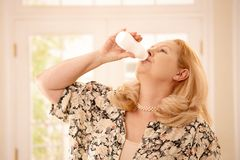 Woman drinking yogurt in kitchen Stock Photo