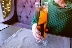 Woman drinks alcohol cocktail in cafe. Hands close-up. stock photography