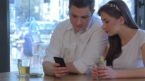 Woman drinks cocktail near the man at the cafe. Pretty woman drinking cocktail near the caucasian man at the cafe. Young brunette guy talking with beautiful girl stock footage