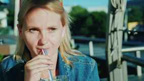 A woman drinks a cocktail from a straw. Relax on the summer terrace in the cafe. 4K video stock footage