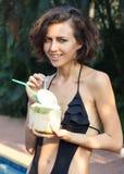 Woman drinks coconut. Woman in bikini drinks fresh coconut with strobe Royalty Free Stock Photos