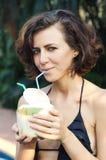 Woman drinks coconut. Woman in bikini drinks fresh coconut with strobe Royalty Free Stock Image