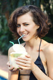 Woman drinks coconut. Woman in bikini drinks fresh coconut with strobe Royalty Free Stock Photo