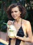 Woman drinks coconut. Woman in bikini drinks fresh coconut with strobe Stock Image