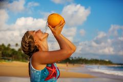 A woman drinks coconut at the seashore at sunset Royalty Free Stock Image