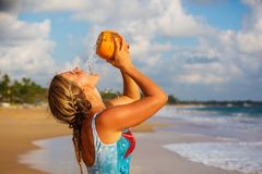 A woman drinks coconut at the seashore at sunset Stock Photography