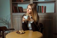 Woman drinks coffee with coockies Stock Photos