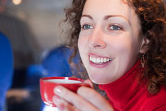 Woman drinks coffee from cup on airplane. Young woman drinks coffee from red cup on airplane, shallow depth of focus stock photography