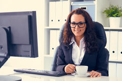 Woman drinks coffee in office Stock Photos