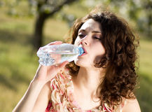 Woman drinks cold water in spring garden Stock Image
