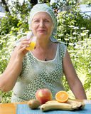 Woman drinks fresh orange juice Royalty Free Stock Photography