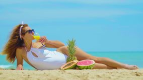 The woman drinks fresh orange juice background the sea. Young beautiful woman lying by the sea on the sand, drinks stock footage