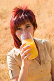 Woman drinks glass of juice. Woman in a field drinking natural orange juice stock image
