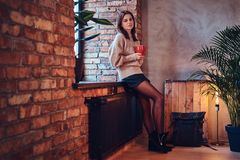 A woman drinks hot coffee in a room with loft interior. A brunette female dressed in a brown long neck jacket drinks hot coffee in a room with loft interior Royalty Free Stock Image
