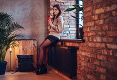 A woman drinks hot coffee in a room with loft interior. A brunette female dressed in a brown long neck jacket drinks hot coffee in a room with loft interior Royalty Free Stock Photos