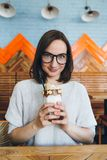 Woman drinks milkshake beautifully decorated with cream and cookies stock photography