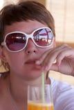 Woman drinks orange juice Royalty Free Stock Photography