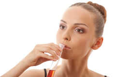 Woman drinks red liquid from a test tube Stock Photo