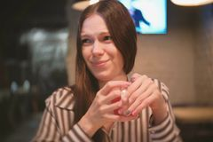 Woman drinks a sour drink, looks at the camera. royalty free stock image