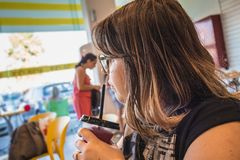 Woman drinks sweet shaved ice and looks away at ice cream parlor.  Stock Photo