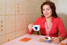 A woman drinks tea. And eats an ice-cream stock photography