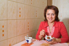 A woman drinks tea. And eats an ice-cream Stock Image