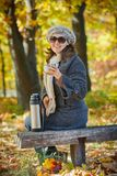 Woman drinks tea in autumn park Stock Photo