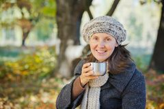 Woman drinks tea in autumn park Royalty Free Stock Photography
