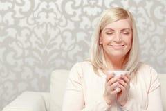 Woman drinks tea on the sofa Stock Photos