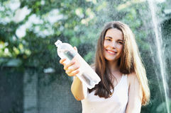 Woman drinks water. Beautiful young woman drinks water from a bottle Royalty Free Stock Image