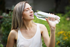 Woman drinks water. Beautiful young woman drinks water from a bottle Stock Photo