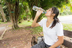 Woman drinks water from bottle in the park. Beautiful young woman drinks water from bottle in the park Royalty Free Stock Photo