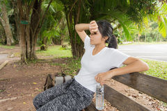 Woman drinks water from bottle in the park. Thirsty woman drinks water from bottle in the park Royalty Free Stock Images