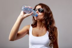 Woman drinks water from bottle. Woman drinks water from plastic bottle Stock Images