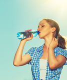 Woman drinks water from a bottle in the summer outdoors on the s. Young woman drinks water from a bottle in the summer outdoors on the sky Royalty Free Stock Photo