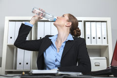Woman drinks water in the office Stock Image