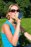 The woman drinks water from a plastic bottle. The beautiful young woman on the nature drinks water Stock Photography