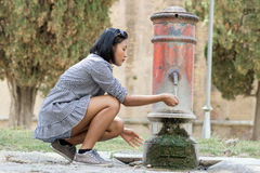Woman drinks water from a pumps. Woman drinks water from street pumps Royalty Free Stock Photos