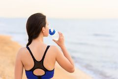 Woman drinks water on the sea beach stock photo