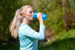 Woman drinks water in a sport dress. Young woman drinks water in a sport dress Royalty Free Stock Images
