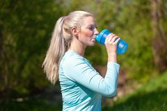 Woman drinks water in a sport dress. Young woman drinks water in a sport dress Royalty Free Stock Photography